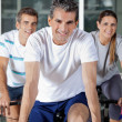 Three On Exercise Bikes — Stock Photo #13152028