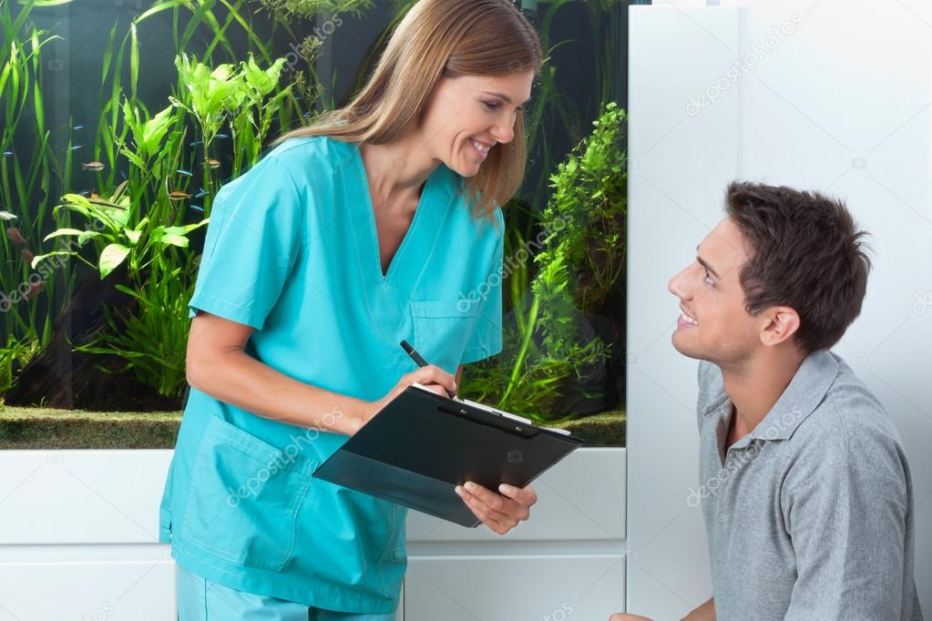 Happy female dentist with clipboard looking at male patient in clinic — Stock Photo #13152117