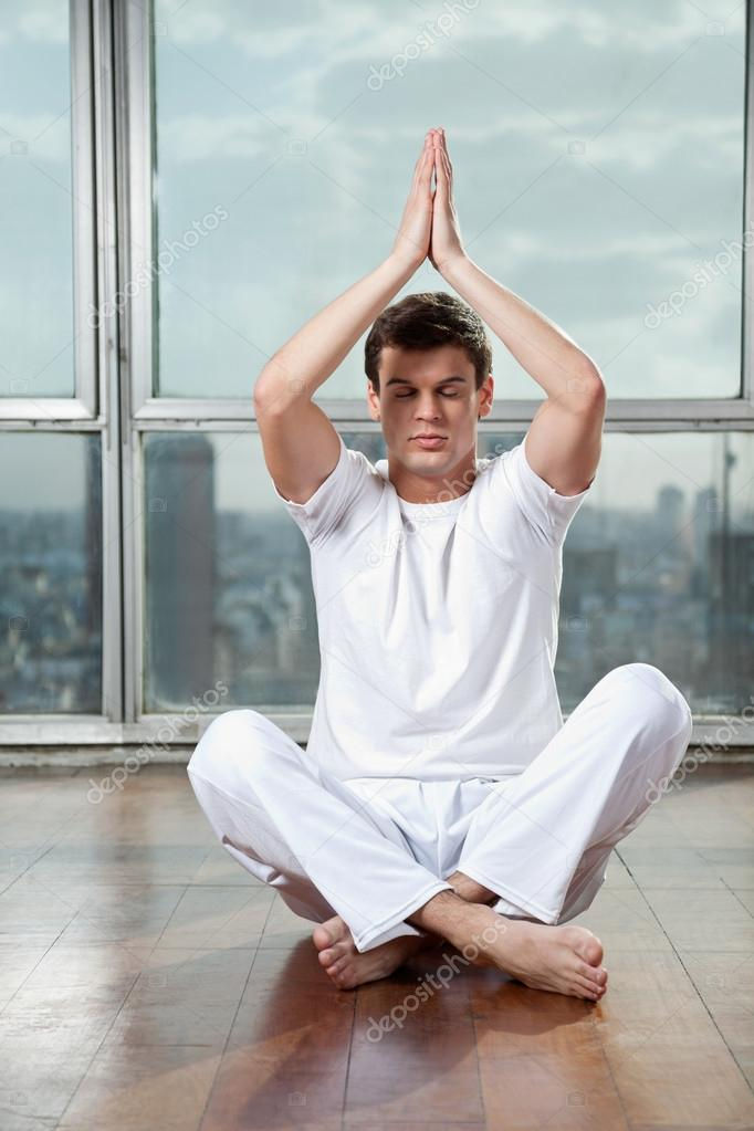 Full length of a young man practicing yoga with hands raised at gym — Stock Photo #13152588