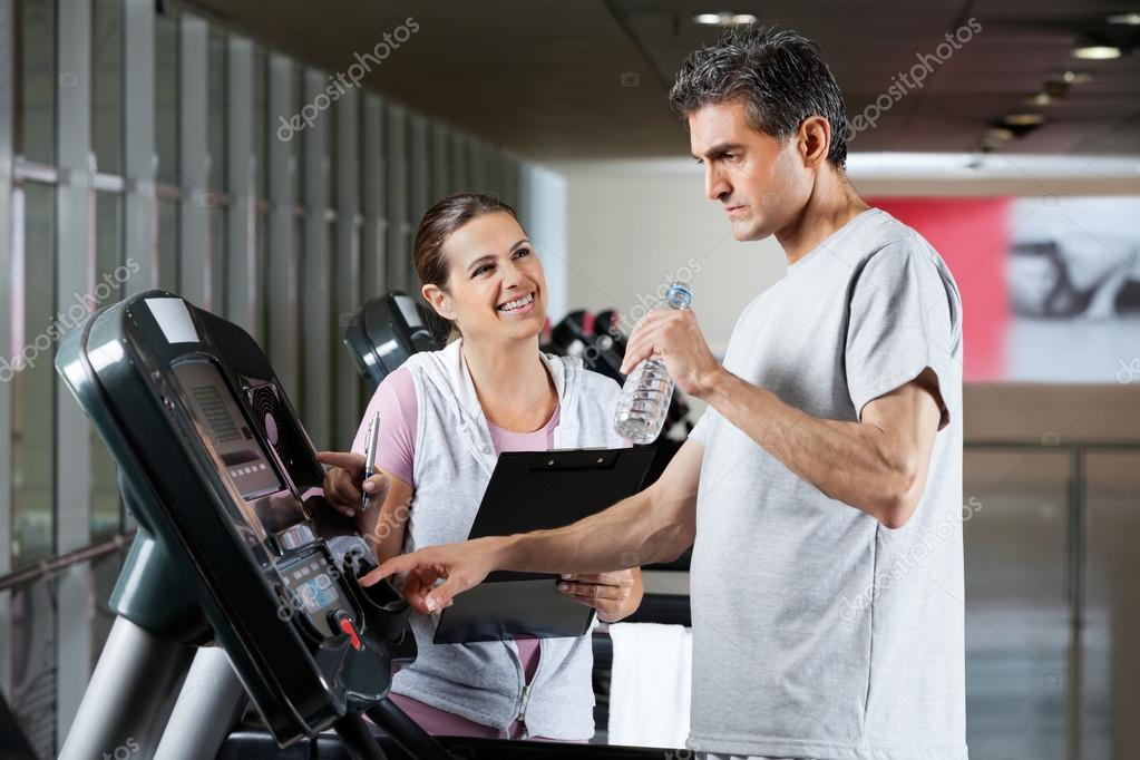 Happy female instructor looking at male client on treadmill drinking water in health center  Stock Photo #13153043