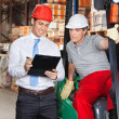 Supervisor Showing Clipboard To Foreman - Stock Photo