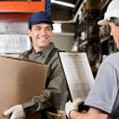 Warehouse Worker Looking At Supervisor With Clipboard - Stock Photo