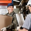 Stock Photo: Warehouse Worker Looking At Supervisor With Clipboard