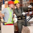 Foreman Showing Something To Coworker At Warehouse - Stok fotoğraf