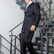 Businessman Walking Down The Stairs - Stock Photo