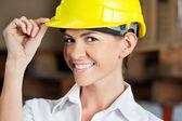 Female Supervisor Touching Hardhat At Warehouse — Stock Photo