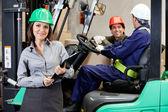 Vertrouwen vrouwelijke toezichthouder met heftruck chauffeur in magazijn — Stockfoto