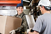 Warehouse Worker Looking At Supervisor With Clipboard — Stockfoto