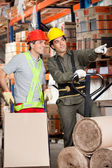 Foreman Showing Something To Coworker At Warehouse — Stock Photo