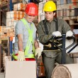 Stock Photo: ForemShowing Something To Coworker At Warehouse