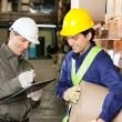 Foreman Looking At Supervisor Writing Notes - Stockfoto