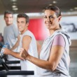 Woman And Men Running On Treadmill In Fitness Center - Stock Photo