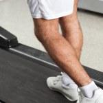 Man Walking On Treadmill In Health Club — Stock Photo #14213811