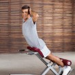Man Exercising On Machine In Health Club — Stock Photo #14214273