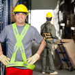 Mid Adult Foreman With Hands On Hips At Warehouse - Foto Stock