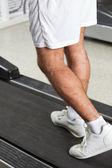 Hombre caminando en la caminadora en health club — Foto de Stock