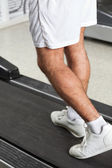 在健身俱乐部的跑步机上行走的人 — 图库照片