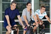 Homens e mulheres em bicicletas de exercício — Foto Stock