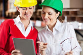 Female Supervisors Using Digital Tablet At Warehouse — Stock Photo