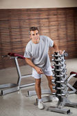 Man Standing By Dumbbells In Rack — Stock Photo