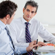 Stock Photo: Businessmen Discussing Paperwork In Office