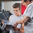 Instructor Guiding Man To Fill The Membership Form - Stock Photo