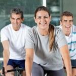 Men And Woman On Exercise Bikes — Stock Photo #14266419