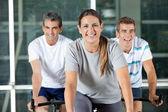 Men And Woman On Exercise Bikes — Stock Photo