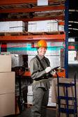 Supervisor Writing On Clipboard At Warehouse — Stock Photo