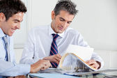 Businessmen Discussing Paperwork In Office — Stock Photo
