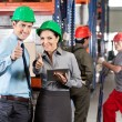 Supervisors Gesturing Thumbs Up At Warehouse - Stock Photo