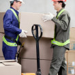 Stock Photo: Foremen Lifting Cardboard Box At Warehouse