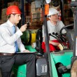 Supervisor With Clipboard Instructing Forklift Driver - Zdjęcie stockowe