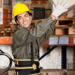 Foreman Lifting Cardboard Box At Warehouse - Stock Photo