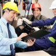Foto Stock: Male Supervisor Communicating With Forklift Driver And Foreman