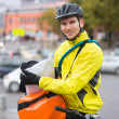 Male Cyclist Putting Package In Courier Bag On Street — Stock Photo