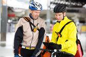 Kurye teslim erkekler dijital tablet kullanarak bisiklet ile — Stok fotoğraf