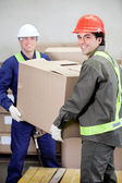 прорабы, лифтинг картонную коробку на складе — Стоковое фото