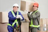 Voormannen laden van kartonnen dozen in magazijn — Stockfoto
