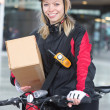 Stock Photo: Female Cyclist With Cardboard Box And Courier Bag On Street