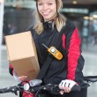 Female Cyclist With Cardboard Box And Courier Bag On Street - Stock Photo