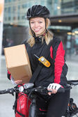Karton kutu ve kurye çantası sokakta kadın bisikletçi — Stok fotoğraf