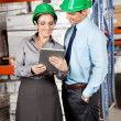 Female Supervisor And Colleague Using Digital Tablet - Stock Photo