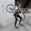 Male Cyclist With Bicycle On His Shoulder Walking Up Steps — Stockfoto