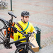 Courier Delivery Man With Package And Bicycle Walking Up Steps - Foto Stock