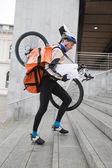 Kurye teslimat adam bisiklet ve merdivenlerden yukarı yürümek sırt çantası — Stok fotoğraf