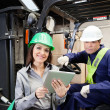 Female Supervisor And Forklift Driver With Digital Tablet - Stock Photo