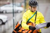 Genç adam sokakta paket ve kurye çantası — Stok fotoğraf