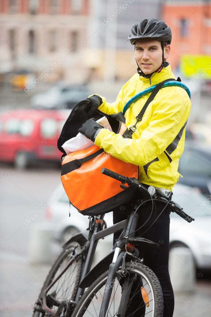 Portrait of young male cyclist putting package in courier bag on street — Stock Photo #15610693