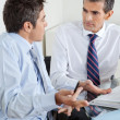 Young Businessman And Colleague Discussing Paperwork - Stock Photo